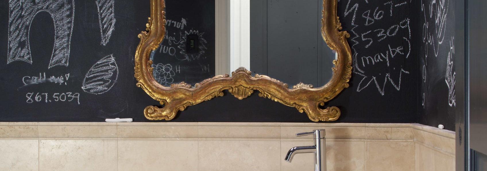 Ornate gold-leaf mirror in powder room